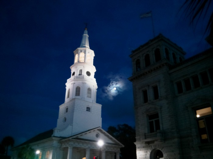 A full moon framed between St. Michaels Church and the US Post Office in Charleston, SC