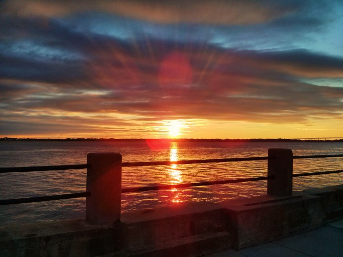 The sun setting with a spray of rays along the Ashley River in Charleston, SC