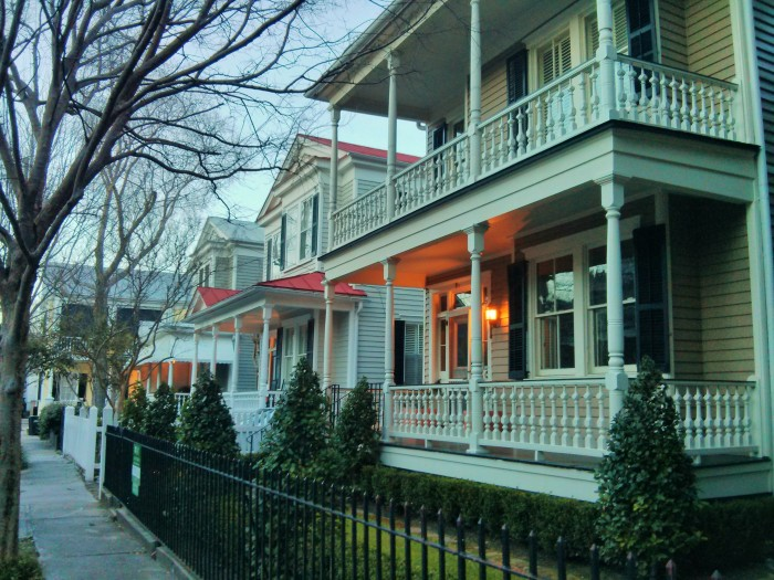 The setting sun provides a wonderful glow on a beautiful row of Charleston, SC houses.
