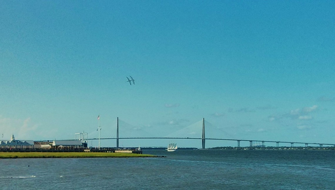 An amazing bridge, an historic aircraft carrier, a tall-masted schooner and pelicans soaring over it all = Charleston Harbor.