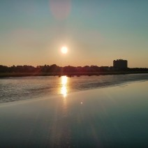 The sun rising over the peninsula of Charleston, SC is beautifully reflected in the pluff mud flats along the Ashley River.
