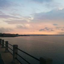 The sun starts to light up the sky above Charleston Harbor, as seen from the High Battery.