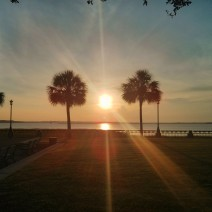 The sun rising over Charleston Harbor and Castle Pinckney, as seen from Waterfront Park.