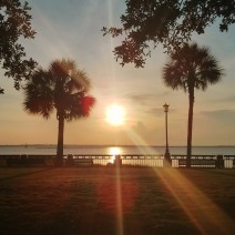 The sun rising over Charleston Harbor as seen from Waterfront Park.