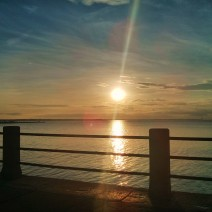 The sun rising over Charleston Harbor as seen from the High Battery near the tip of the Charleston peninsula.