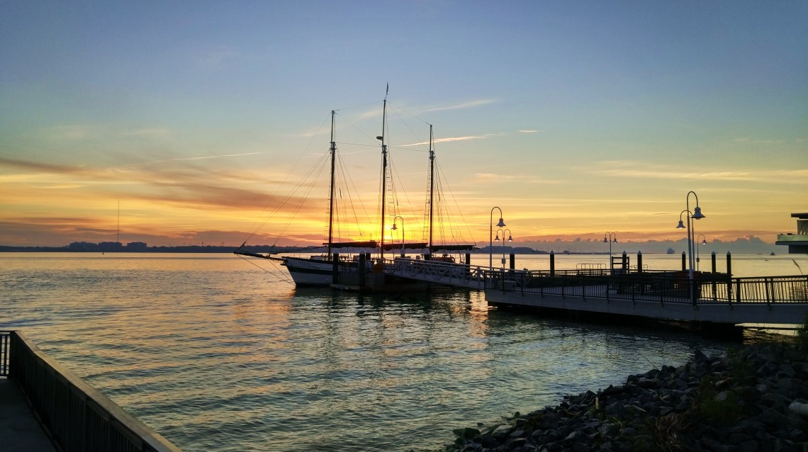 The sun rising over Charleston Harbor is captured through the rigging of the three-masted schooner Pride.