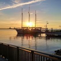 The sun rises over Charleston Harbor, lighting up the three-masted Schooner Pride.