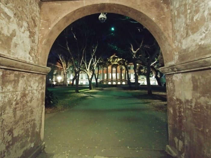 The Porters Lodge, built about 1850, framing a nighttime view of Randolph Hall (built 1829-30) and the Cistern at the College of Charleston.