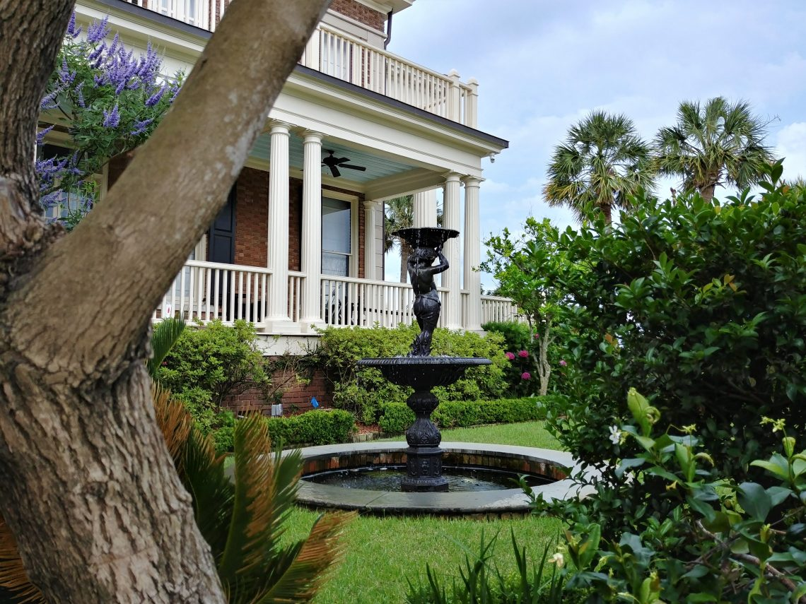 "This wonderful Charleston garden is at the very first house built on Murray Boulevard. The ceiling of the porch is painted in ""Haint Blue."" The Gullah-Geechee communities, found in coastal South Carolina and Georgia, believed that the blue would keep the spirits of the dead (the haints) from entering the house. Now common in Charleston and across the South, it may or may not work on the spirits, but it sure does make for a pretty porch."