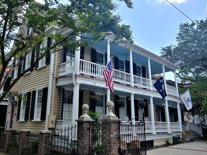 "This beautiful Charleston single house on Tradd Street is nicely decked out in the American, South Carolina and US Army flags. It's called a ""single house"" because it is only one room wide. No matter how big or small a single house may be, that is one of their main distinguishing characteristics."