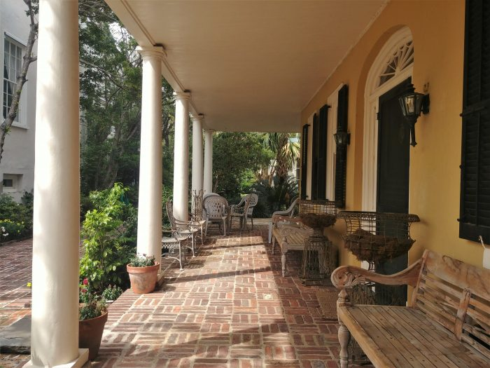 This cool seating area is under the house's piazza -- the side porch of a Charleston single house. A piazza is a type of porch, but not all porches are piazzas! You can find this one on South Battery.