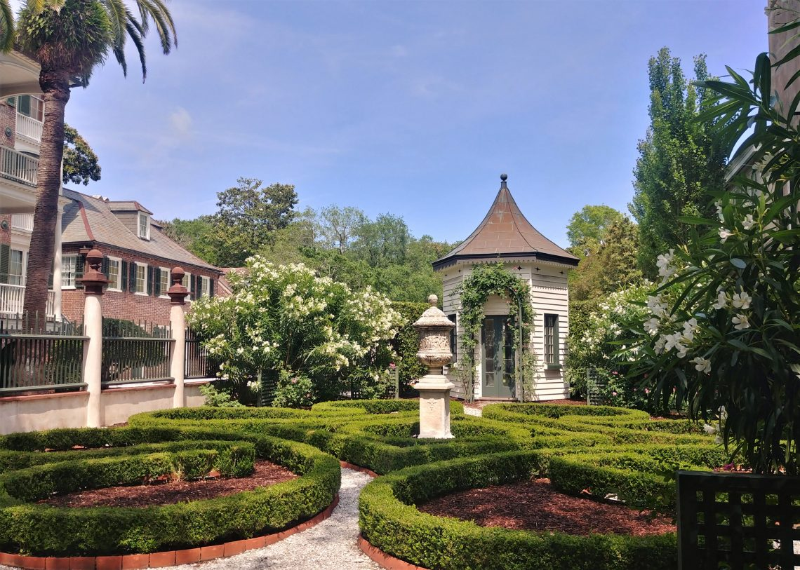 """This garden belongs to the Simmons-Edwards House on Legare Street, more commonly referred to as the Pineapple Gates House. The stone pineapples are a symbol for """"welcome."""""""