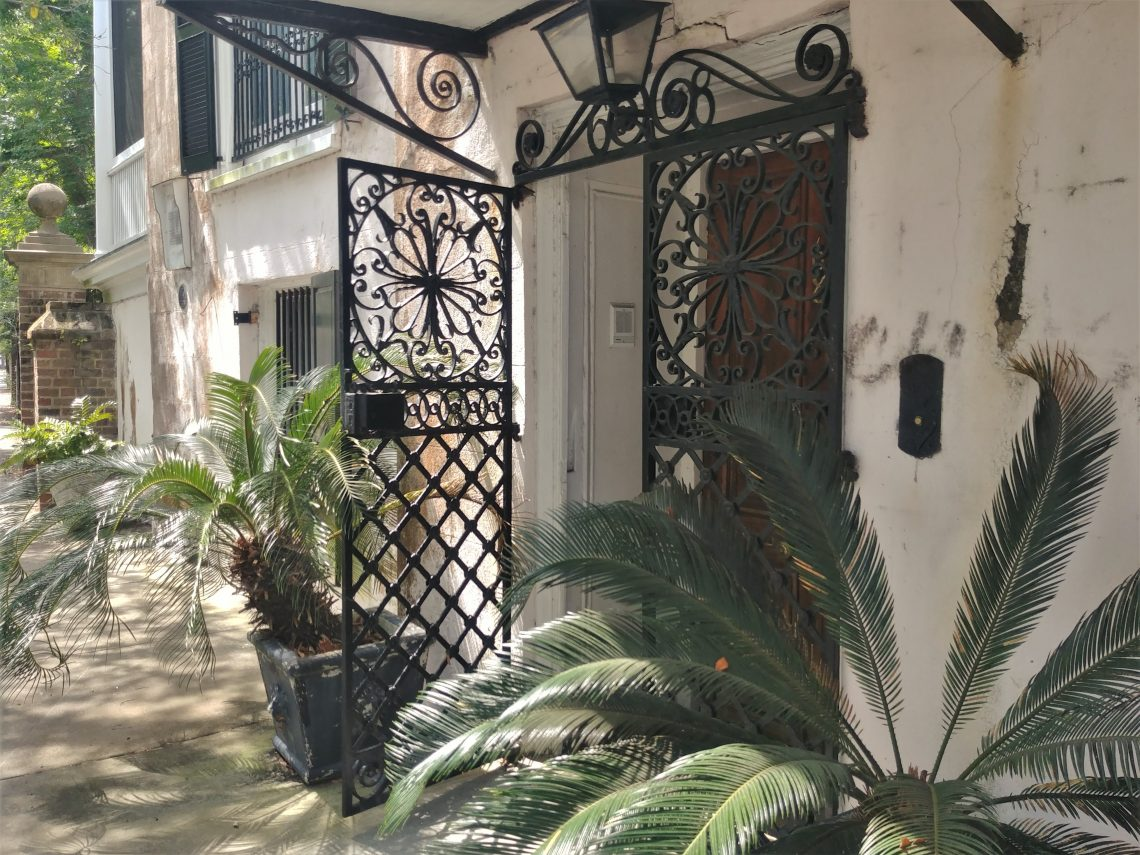 Unlike for other houses of its age with side piazzas (c. 1800),  this centrally located street front door is the main entrance to the house. After passing through its beautiful wrought iron gates, the door leads to a staircase that provides access to the main floor. You can find it on South Battery.