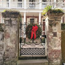 """This wreath-wearing gorgeous gate can be found on Church Street, along """"The Bend."""" If you look closely, you will see that the front door to the house is not symmetrical with the gate -- as the house was damaged by a hurricane in 1752 and the door migrated to the right in the subsequent repairs."""