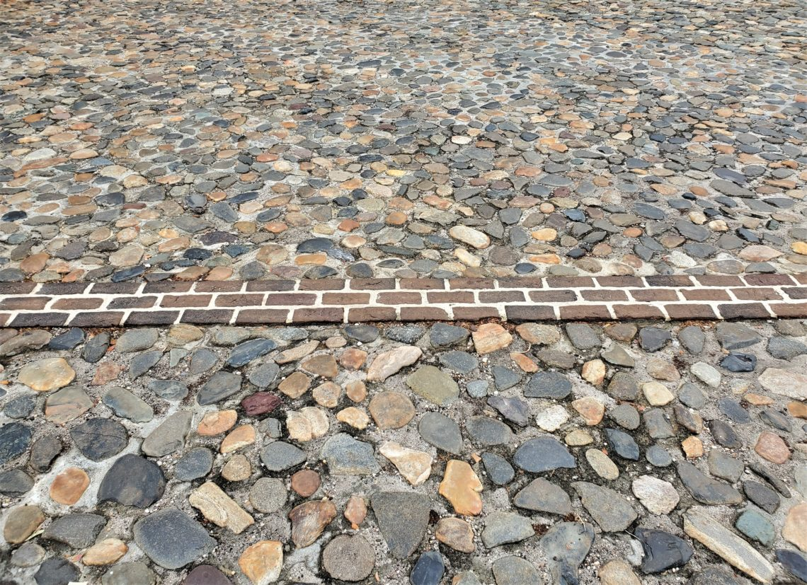 "This line of bricks represents where the wall (more specifically, a ""redan"") of the original walled city of Charleston once was. It was identified during an archaeological dig by the ""Walled City Task Force."" You can find it along the top of South Adger's Wharf and through the adjacent parking lot. Pretty cool."