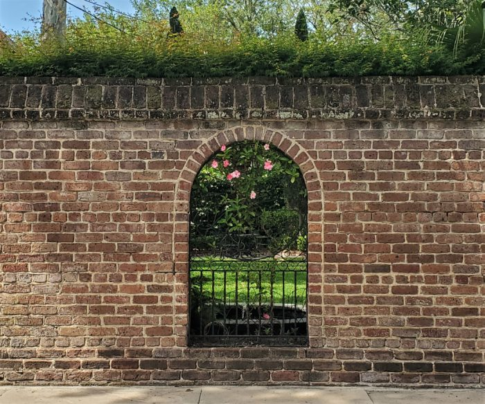 This cool wall with its window into the garden is on Lamboll Street. In the warmer weather it is always great to see the mandevilla flowering along the iron.